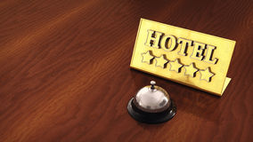 Luxury hotel. Chrome service bell and golden hotel plate on wooden countertop with copyspace , Five star hotel Royalty Free Stock Photography