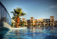 Luxury Hotel Complex Travel Africa. Luxury hotel complex - swimming pool, bridge and palm trees near coral reef of the Red sea, Egypt Royalty Free Stock Photography