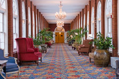 Luxury hotel hallway. A luxurious, well decorated, elegant hallway with comfortable chairs, potted plants and chandeliers royalty free stock photography