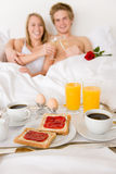 Luxury hotel honeymoon breakfast - couple in bed. Luxury hotel honeymoon breakfast - couple in white bed together Stock Photo