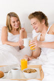 Luxury hotel honeymoon breakfast - couple in bed. Luxury hotel honeymoon breakfast - couple in white bed together Stock Photos