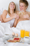 Luxury hotel honeymoon breakfast - couple in bed. Luxury hotel honeymoon breakfast - couple in white bed together Stock Image