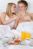 Luxury hotel honeymoon breakfast - couple in bed. Luxury hotel honeymoon breakfast - couple in white bed together Royalty Free Stock Image