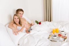 Luxury hotel honeymoon breakfast - couple in bed. Luxury hotel honeymoon breakfast - couple in white bed together Royalty Free Stock Images