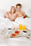 Luxury hotel honeymoon breakfast - couple in bed. Luxury hotel honeymoon breakfast - couple in white bed together Royalty Free Stock Photography