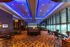 Luxury hotel lobby. Floored with golden carpet, nicely deocrated with a blue lit ceiling with small tables facing the outdoor all over the big room stock image