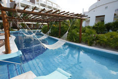 Luxury hotel with long pool and hammocks. Stock Image