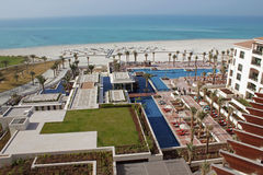 Luxury hotel pool and white sandy beach. Aerial view of a luxury hotel pool and stunning white sandy beach and turquoise sea Stock Image