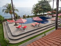 Outdoor pool in the hotel. Luxury hotel,resort near at sea with pool among the palm trees. Luxurious open air swimming pool at resort. Swimming pool with Royalty Free Stock Photo