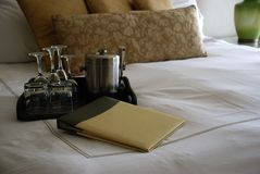 Luxury Hotel Room Bed with Drinks Tray and Menu. Soft shot of a luxury hotel room at one of the leading resorts in the world Stock Image