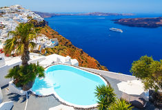 Luxury hotel with sea view. White architecture on Santorini island, Greece. Beautiful view on sea and cruise ship Royalty Free Stock Photo