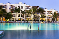 Luxury hotel with swimming pool at dusk Royalty Free Stock Images
