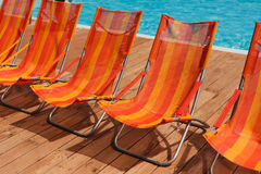 Luxury hotel swimming pool in front of the sea. Red orange chairs cost about elite hotel pool. Nearby pine trees or Christmas trees, wooden floor Stock Photography