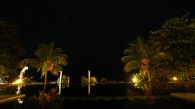 Hotel with a pool in the background of the starry sky. Luxury hotel with a swimming pool and palm trees under the starry sky. Time-lapse, long exposure, sky stock video