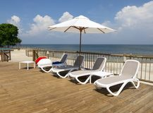 Luxury Hotel Tropical Beach Resort. Tanning deck and chairs at a luxury tropical beach resort. People love to go to the ocean to relax while on vacation or Royalty Free Stock Image