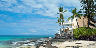 Luxury hotel on untouched sandy beach with palms trees and azure royalty free stock photography