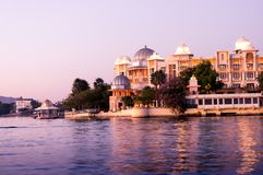 Luxury hotels on the bank of a lake. Luxury hotel on the bank of pichola lake in udaipur. Shot at sunset it showcases the amazing hospitality options for Royalty Free Stock Image