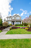Luxury house with beautiful landscaping on a sunny day. Home exterior design royalty free stock photos