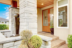 Luxury house entrance porch with stone column trim and stained w. Luxury house entrance porch with stone column trim, stained wood door and window stock photo