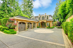 Luxury house exterior. Luxury house with beautiful curb appeal. View of three car garage and driveway royalty free stock photography