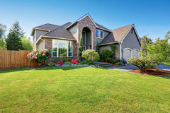 Luxury house exterior with brick and siding trim and double garage. Well kept garden around. Northwest, USA stock photos