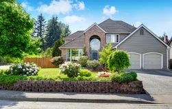 Luxury house exterior with brick and siding trim and double garage. Well kept garden around. Northwest, USA royalty free stock photo