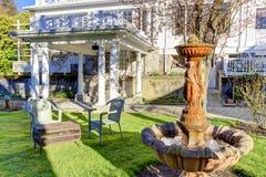 Luxury house exterior. Fountain in backyard garden Stock Photography