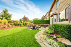 Luxury house exterior with impressive backyard landscape design. Impressive backyard landscape design with cozy patio area Stock Photo