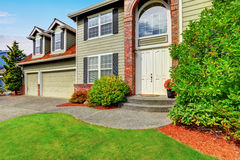 Luxury house exterior with red brick trim and arched entry. Stock Photography