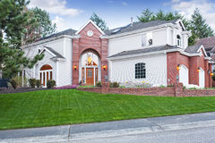 Luxury house exterior with three car garage and driveway. Luxury house exterior with red brick wall trim, with three car garage and driveway royalty free stock images