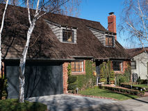 Luxury house and frontyard. Luxury house with frontyard and two attic windows. Large wooden shingle roof and red chimney. Brick wall covered with ivy Stock Images