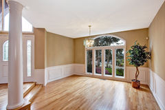 Luxury house interior. Empty entrance hallway. Luxury house interior. Bright  empty hallway with large window and column. Decorated with fake tree in corner Royalty Free Stock Photo
