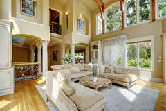 Luxury house interior. Living room. Impressive high ceiling living room with antique furniture, columns and balcony stock images