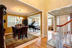 Luxury house interior with open floor plan. Dining area and living room with grand piano stock photography