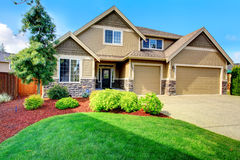 Luxury house ith beautiful curb appeal. Clapboard siding house  with stone trim. View of  entrance porch, beautiful flower bed with green lawn, bushes and fir Royalty Free Stock Image