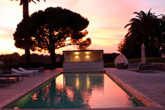 Luxury house pool at sunset Stock Photos