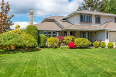 Luxury house on a sunny day. Luxury house with freshly mown grass lawn. Home exterior stock photo