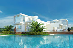 Luxury house with a tropical garden and pool. Luxury modern white house with angular walls and large windows overlooking a tropical landscaped garden with palm royalty free stock photography
