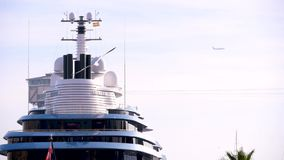 Luxury huge yacht in the parking lot in Barcelona on the background of a flying airplane.