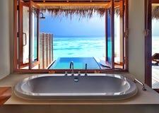 Luxury interior on beach resort. Luxury beautiful interior design on beach resort, window view from bathroom on clear blue sea, summer vacation on Maldives Stock Photo