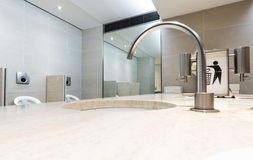 Luxury interior clean mens toilet. Wide angle focus on rounded t. Aps and bin it sign Stock Photos