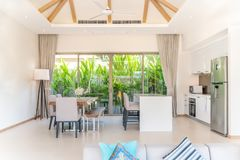 Luxury interior design in living room of pool villas. Airy and bright space with high raised ceiling and kitchen area with dining. Table royalty free stock photos