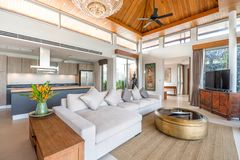 Luxury interior design in living room of pool villas. Airy and bright space with high raised ceiling and wooden dining table. Luxury interior design in living royalty free stock photo
