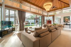 Luxury interior design in living room of pool villas. Airy and bright space with high raised ceiling and wooden dining table. Luxury interior design in living royalty free stock photos