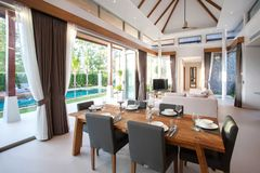 Luxury interior design in living room of pool villas. Airy and bright space with high raised ceiling and wooden dining table. Luxury interior design in living stock photos