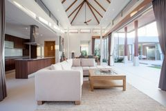 Luxury interior design in living room of pool villas. Airy and bright space with high raised ceiling and wooden dining table. Luxury interior design in living royalty free stock photography