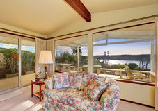 Luxury interior of living room with vaulted ceiling. Floral patterned sofa and perfect water view from the windows. Northwest, USA royalty free stock photo