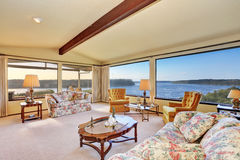 Luxury interior of living room with vaulted ceiling. Floral patterned sofas, nice coffee table and perfect water view from the windows. Northwest, USA royalty free stock photos