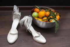 Luxury ivory wedding accessories for bride. And Bright deep orange Clementine or Mandarins  in a bowl Stock Photo