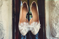 Luxury ivory wedding shoes with lace flower on it, for bride, selective focus. Stock Photos